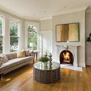 サンフランシスコの中サイズのヴィクトリアン調のおしゃれな独立型リビング (ベージュの壁、淡色無垢フローリング、標準型暖炉、漆喰の暖炉まわり) の写真