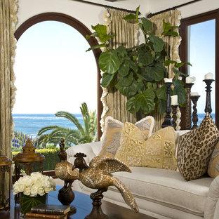 サンディエゴの広い地中海スタイルのおしゃれなLDK (フォーマル、白い壁、濃色無垢フローリング、両方向型暖炉、タイルの暖炉まわり、茶色い床、テレビなし) の写真