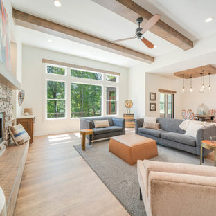 This is an example of a large eclectic open concept living room in Grand Rapids with white walls, medium hardwood floors, a standard fireplace, brown floor and exposed beam.