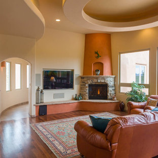 Mid-sized southwest open concept dark wood floor living room photo in Albuquerque with beige walls, a standard fireplace, a stone fireplace and a wall-mounted tv