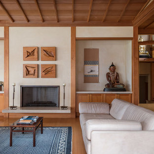 Design ideas for a large asian open concept living room in Hawaii with a music area, beige walls, light hardwood floors, a standard fireplace, a metal fireplace surround, no tv and brown floor.