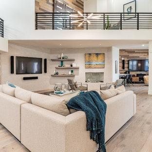 フェニックスの巨大なモダンスタイルのおしゃれなリビングロフト (白い壁、淡色無垢フローリング、タイルの暖炉まわり、壁掛け型テレビ、ベージュの床) の写真