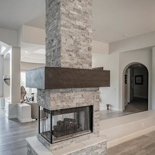 Imagen de salón abierto, moderno, pequeño, sin televisor, con paredes beige, suelo de baldosas de porcelana, chimenea de doble cara y marco de chimenea de piedra