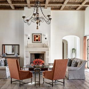 Medelhavsstil inredning av ett allrum med öppen planlösning, med ett finrum, vita väggar, mellanmörkt trägolv, en standard öppen spis, en spiselkrans i sten och brunt golv