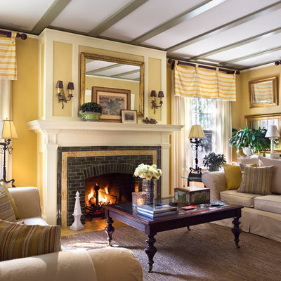 Elegant enclosed living room photo in New York with yellow walls, a standard fireplace and a brick fireplace