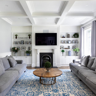 This is an example of a transitional living room in Melbourne with white walls, dark hardwood floors, a standard fireplace, a wall-mounted tv, brown floor, coffered and decorative wall panelling.