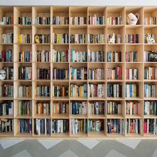 Foto på ett mellanstort funkis allrum med öppen planlösning, med ett bibliotek, vita väggar, linoleumgolv, en öppen vedspis och en spiselkrans i sten