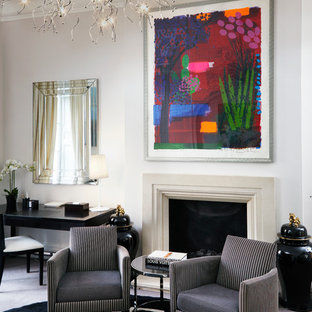 This is an example of a medium sized contemporary formal enclosed living room in London with white walls, carpet, a standard fireplace and a plastered fireplace surround.