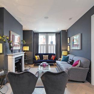 Immagine di un soggiorno classico di medie dimensioni e chiuso con sala formale, pareti grigie, parquet chiaro, camino classico, cornice del camino in pietra e nessuna TV
