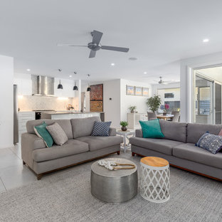 Design ideas for a beach style open concept living room in Other with white walls and grey floor.