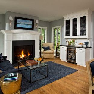 ボストンの小さいトラディショナルスタイルのおしゃれなリビング (グレーの壁、無垢フローリング、標準型暖炉、木材の暖炉まわり、テレビなし、青いソファ) の写真