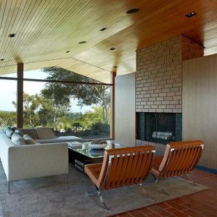 Immagine di un soggiorno moderno aperto con camino classico, cornice del camino in mattoni, pavimento rosso, soffitto a volta e soffitto in legno