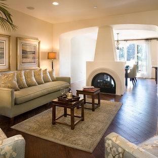 サンタバーバラの中くらいの地中海スタイルのおしゃれなLDK (ベージュの壁、両方向型暖炉、フォーマル、濃色無垢フローリング、漆喰の暖炉まわり、テレビなし) の写真