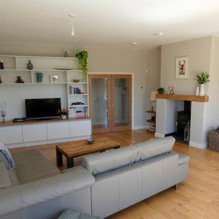 Foto de salón actual, grande, con paredes blancas, estufa de leña, marco de chimenea de hormigón y suelo beige
