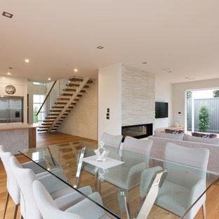 オークランドの大きいコンテンポラリースタイルのおしゃれなLDK (白い壁、淡色無垢フローリング、横長型暖炉、レンガの暖炉まわり、壁掛け型テレビ) の写真