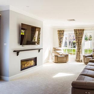 シドニーの中くらいのトラディショナルスタイルのおしゃれなLDK (フォーマル、ベージュの壁、カーペット敷き、漆喰の暖炉まわり、壁掛け型テレビ、ベージュの床、吊り下げ式暖炉) の写真