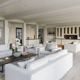 Esempio di un ampio soggiorno stile marinaro aperto con sala formale, pareti bianche, pavimento in compensato, camino classico, cornice del camino in pietra e pavimento bianco