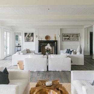 ロサンゼルスの巨大なビーチスタイルのおしゃれなLDK (フォーマル、白い壁、合板フローリング、標準型暖炉、石材の暖炉まわり、白い床) の写真