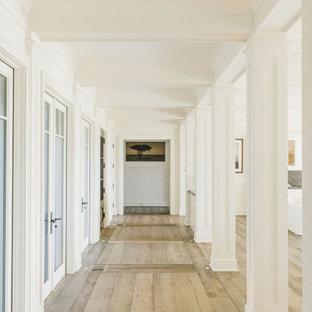 Ispirazione per un ampio soggiorno stile marino aperto con sala formale, pareti bianche, pavimento in compensato, camino classico, cornice del camino in pietra e pavimento bianco