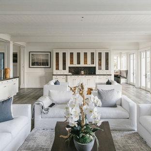 Idee per un ampio soggiorno stile marinaro aperto con sala formale, pareti bianche, pavimento in compensato, camino classico, cornice del camino in pietra e pavimento bianco