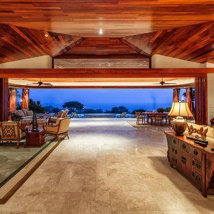 ハワイの巨大なトロピカルスタイルのおしゃれなLDK (ベージュの壁、トラバーチンの床、埋込式メディアウォール) の写真