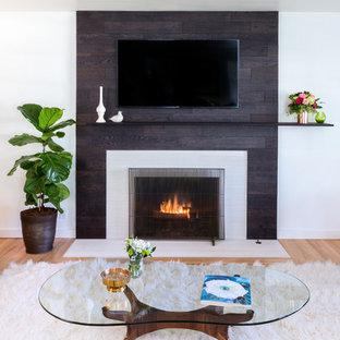 ロサンゼルスの中サイズのミッドセンチュリースタイルのおしゃれなLDK (グレーの壁、淡色無垢フローリング、標準型暖炉、木材の暖炉まわり、壁掛け型テレビ) の写真