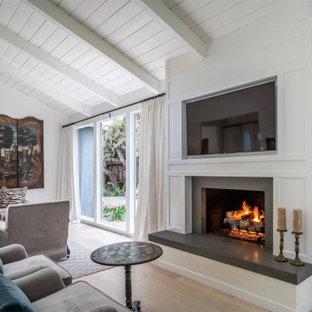 他の地域の中サイズのビーチスタイルのおしゃれなLDK (フォーマル、白い壁、淡色無垢フローリング、標準型暖炉、木材の暖炉まわり、埋込式メディアウォール、ベージュの床) の写真