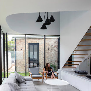 Contemporary open concept living room in Sydney with white walls, concrete floors, no fireplace and grey floor.