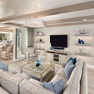 Modelo de salón para visitas abierto, minimalista, grande, sin chimenea, con suelo de madera clara, televisor colgado en la pared y paredes beige