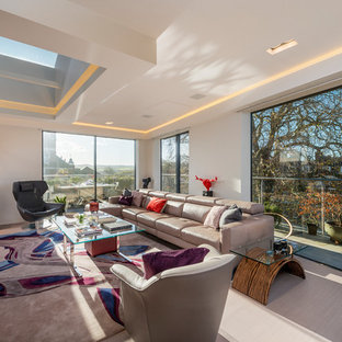 Design ideas for an expansive contemporary formal open plan living room in Devon with beige walls, light hardwood flooring, a concealed tv and beige floors.