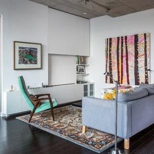 Immagine di un piccolo soggiorno minimalista stile loft con pareti bianche, parete attrezzata, parquet scuro, nessun camino e pavimento marrone