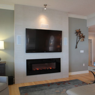 タンパの大きいビーチスタイルのおしゃれなLDK (ベージュの壁、淡色無垢フローリング、横長型暖炉、コンクリートの暖炉まわり、壁掛け型テレビ) の写真