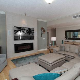 タンパの広いビーチスタイルのおしゃれなLDK (ベージュの壁、淡色無垢フローリング、横長型暖炉、コンクリートの暖炉まわり、壁掛け型テレビ、フォーマル、ベージュの床) の写真