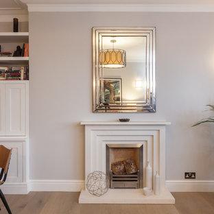 ロンドンの広いエクレクティックスタイルのおしゃれな独立型リビング (フォーマル、グレーの壁、淡色無垢フローリング、標準型暖炉、石材の暖炉まわり、埋込式メディアウォール、茶色い床) の写真