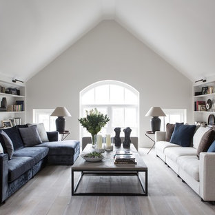 Modern inredning av ett stort allrum med öppen planlösning, med vita väggar, målat trägolv, en väggmonterad TV och grått golv