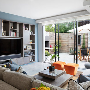 Contemporary living room in London with blue walls, a wall mounted tv and grey floors.