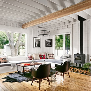 Living room - small country open concept light wood floor living room idea in Austin with a wood stove and white walls