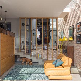 Inspiration pour un petit salon design ouvert avec un mur rouge, un téléviseur dissimulé, un sol gris et un mur en parement de brique.