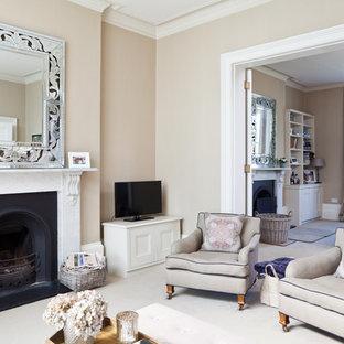 Esempio di un soggiorno vittoriano aperto con sala formale, pareti beige, moquette, camino classico e TV autoportante