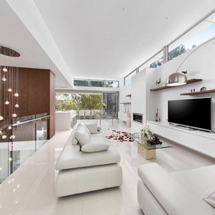 Example of a huge minimalist open concept porcelain floor living room design in Perth with white walls, a metal fireplace and a tv stand