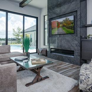 タンパの広いコンテンポラリースタイルのおしゃれなLDK (グレーの壁、磁器タイルの床、標準型暖炉、タイルの暖炉まわり、壁掛け型テレビ、マルチカラーの床) の写真