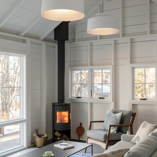 Beach style white floor living room photo in Portland Maine with white walls and a wood stove