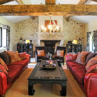Idée de décoration pour un très grand salon champêtre ouvert avec un mur beige, un sol en calcaire, une cheminée standard, un manteau de cheminée en pierre et un sol beige.