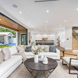 Großes, Offenes Klassisches Wohnzimmer mit grauer Wandfarbe, hellem Holzboden, Wand-TV, beigem Boden und eingelassener Decke in Los Angeles