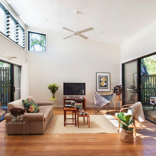 Mid-sized contemporary open concept living room in Brisbane with white walls, medium hardwood floors, a wall-mounted tv and brown floor.