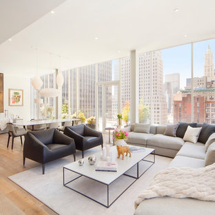 Example of a minimalist formal and open concept medium tone wood floor living room design in New York with white walls
