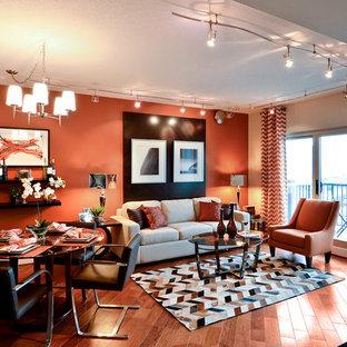 Imagen de salón abierto, contemporáneo, pequeño, con parades naranjas, suelo de madera en tonos medios y televisor colgado en la pared