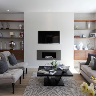 Design ideas for a contemporary formal living room in Hampshire with white walls, light hardwood flooring, a ribbon fireplace, a metal fireplace surround and a wall mounted tv.