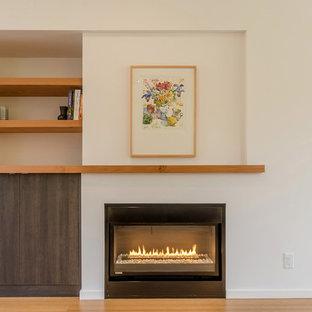 Immagine di un soggiorno minimalista di medie dimensioni e aperto con pareti bianche, pavimento in bambù e parete attrezzata