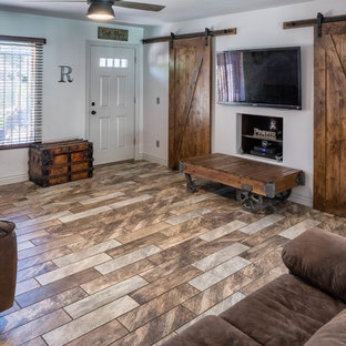フェニックスの中サイズのラスティックスタイルのおしゃれなLDK (白い壁、磁器タイルの床、壁掛け型テレビ、マルチカラーの床) の写真